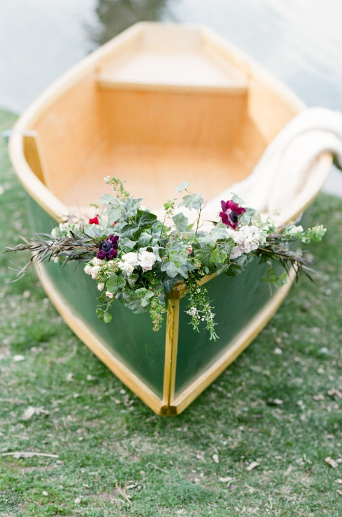 Green rowboat decorated with flowers for an engagement portrait session on the lake in Denver