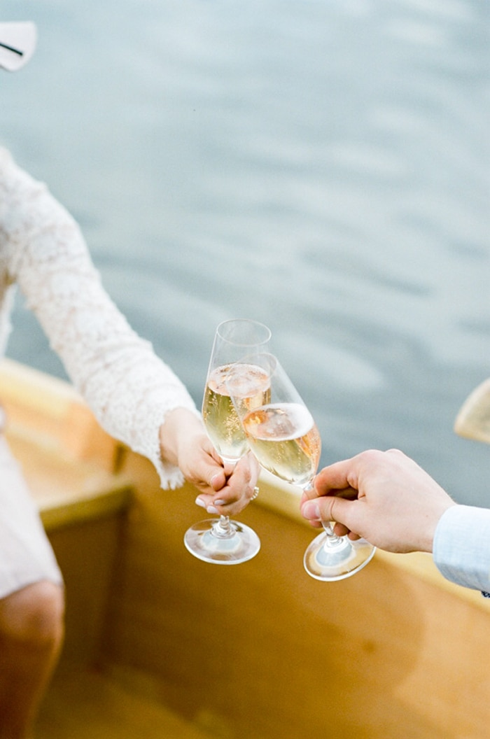 Couple clinking Champagne glasses on a rowboat on a lake in Denver