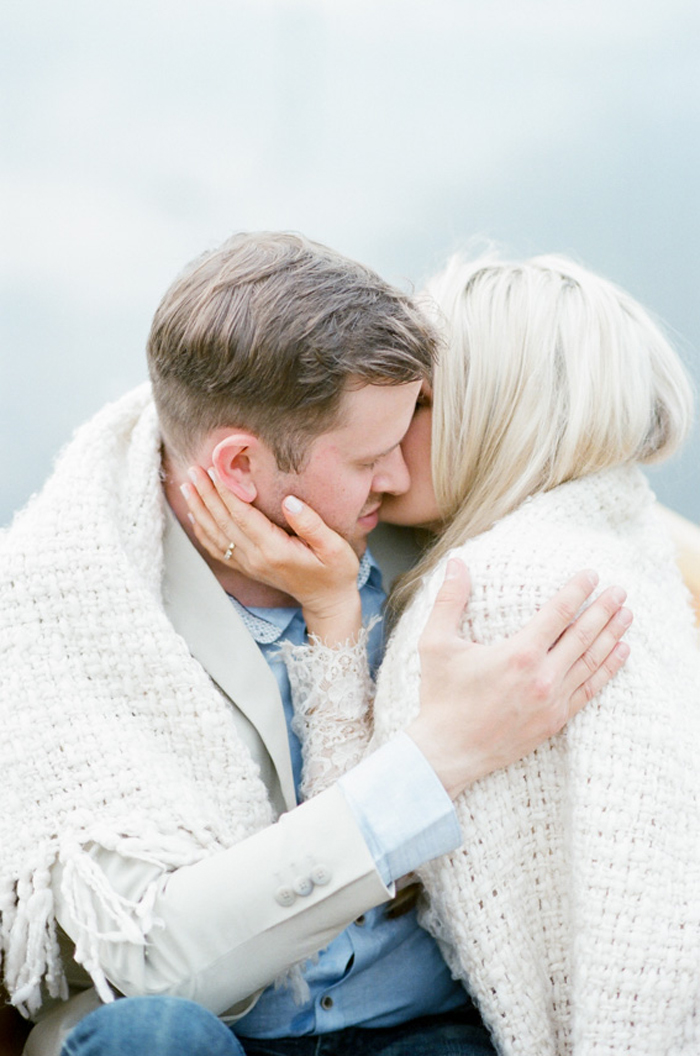 Couple embracing during their Denver engagement portraits on a lake
