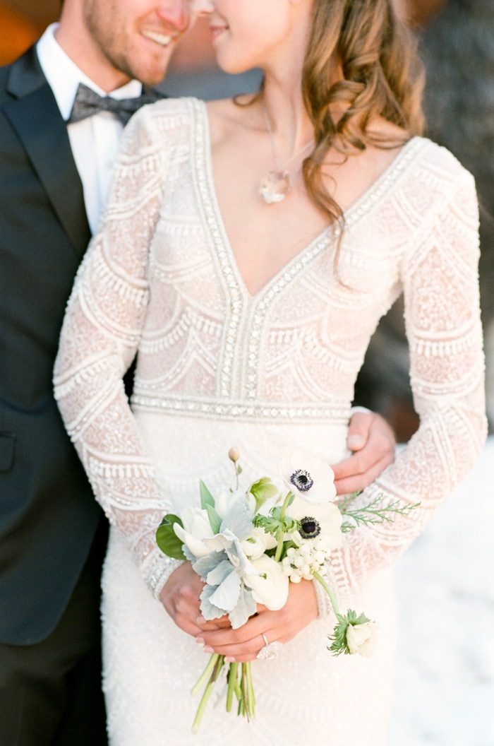 Woman wearing wedding gown adorned with pearls and holding small bouquet