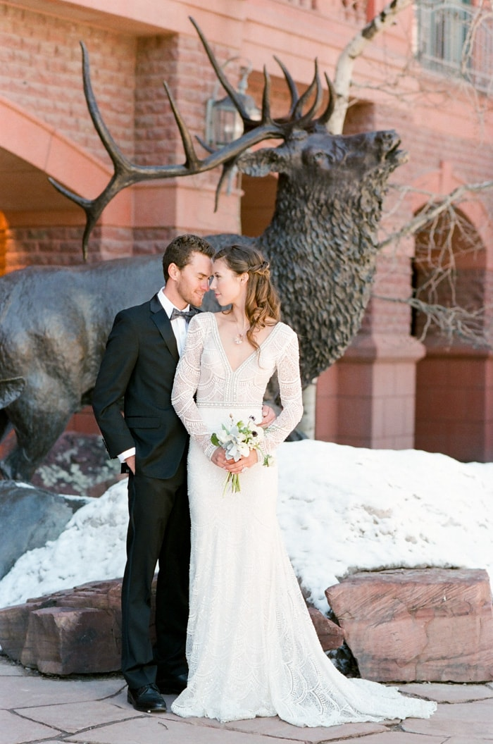 Winter couple portrait with groom behind bride and touching foreheads with elk statue backdrop