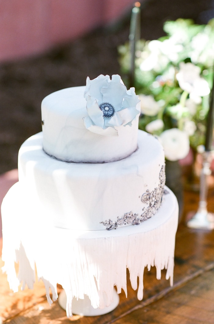Multi-layered white wedding cake with aesthetic flower on top