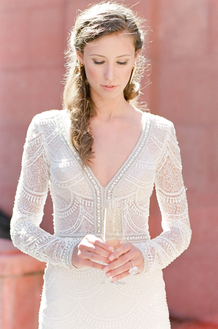 Pondering wedding bride while holding glass of champagne