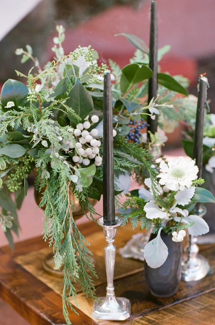 Table centerpiece and floral wedding details with black candles