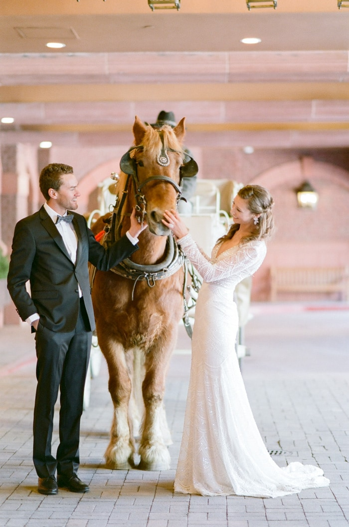 Groom and bride petting a horse