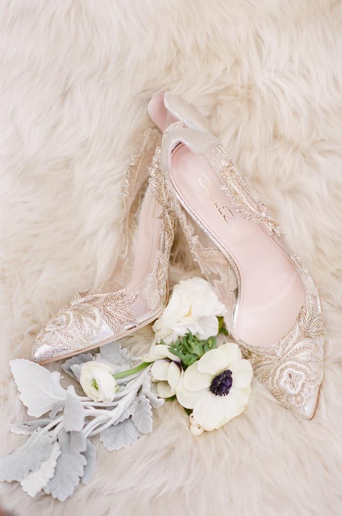 Oscar de La Renta shoes and white flowers laying on fur