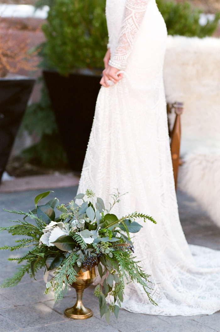 Woman in white wedding dress standing next to vase of greenery