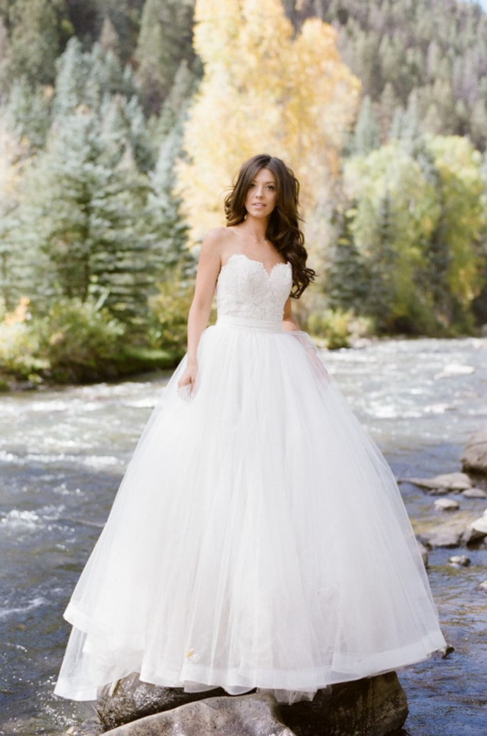 Bride in the Telluride river with her custom Hayley Paige wedding dress
