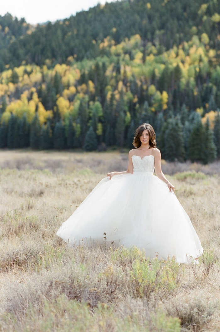Bride in grass field with pine trees in background