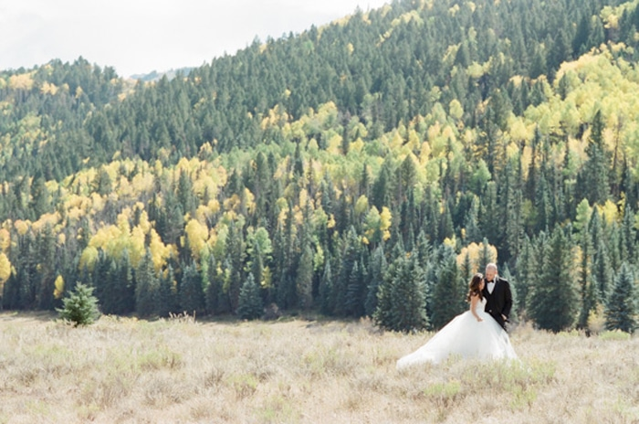 Couple in open field with Telluride forest in background