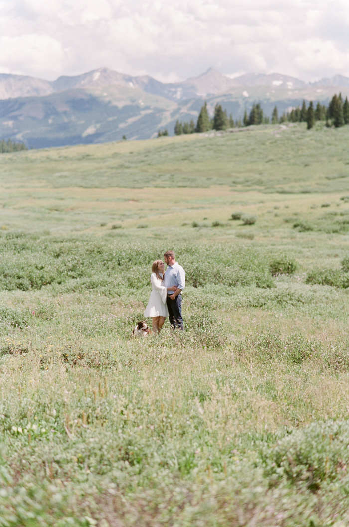 Engaged couple in grassy field with dog at Vail mountain top