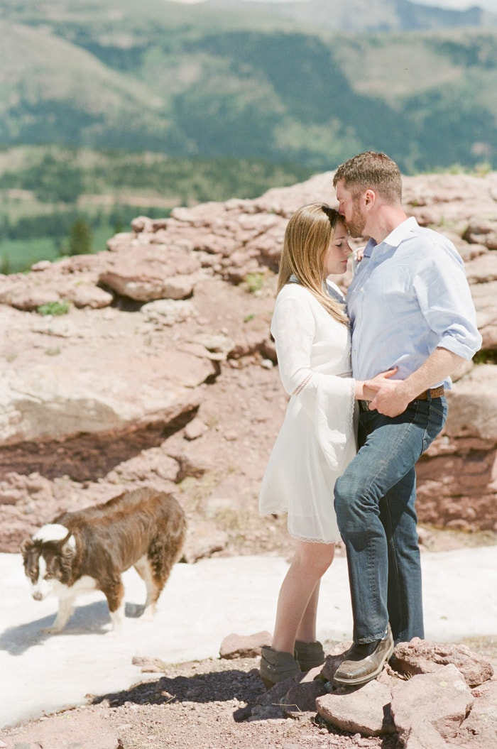 Formal portrait of engaged couple close together with Australian Shepherd on patch of ice