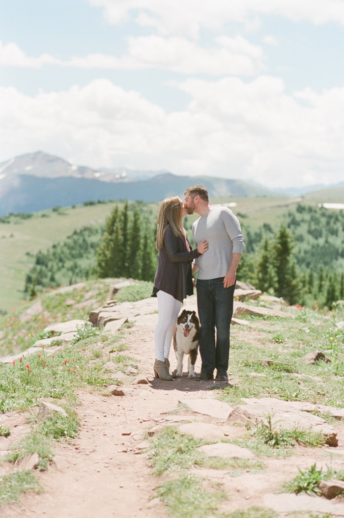Bride and groom kissing on top of Vail mountain next to their dog