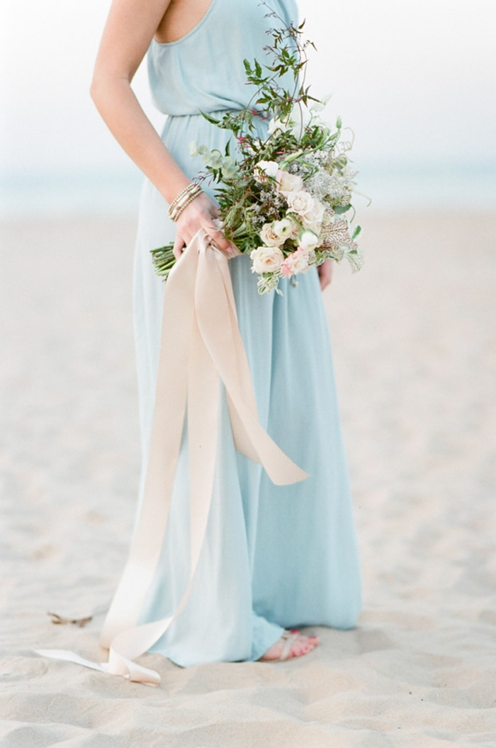 Woman wearing blue dress standing on the beach with bouquet of white flowers