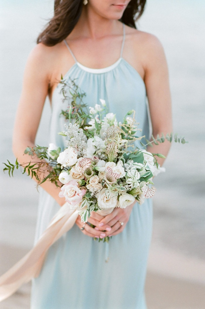 Bride-to-be in blue dress holding an assortment of flowers