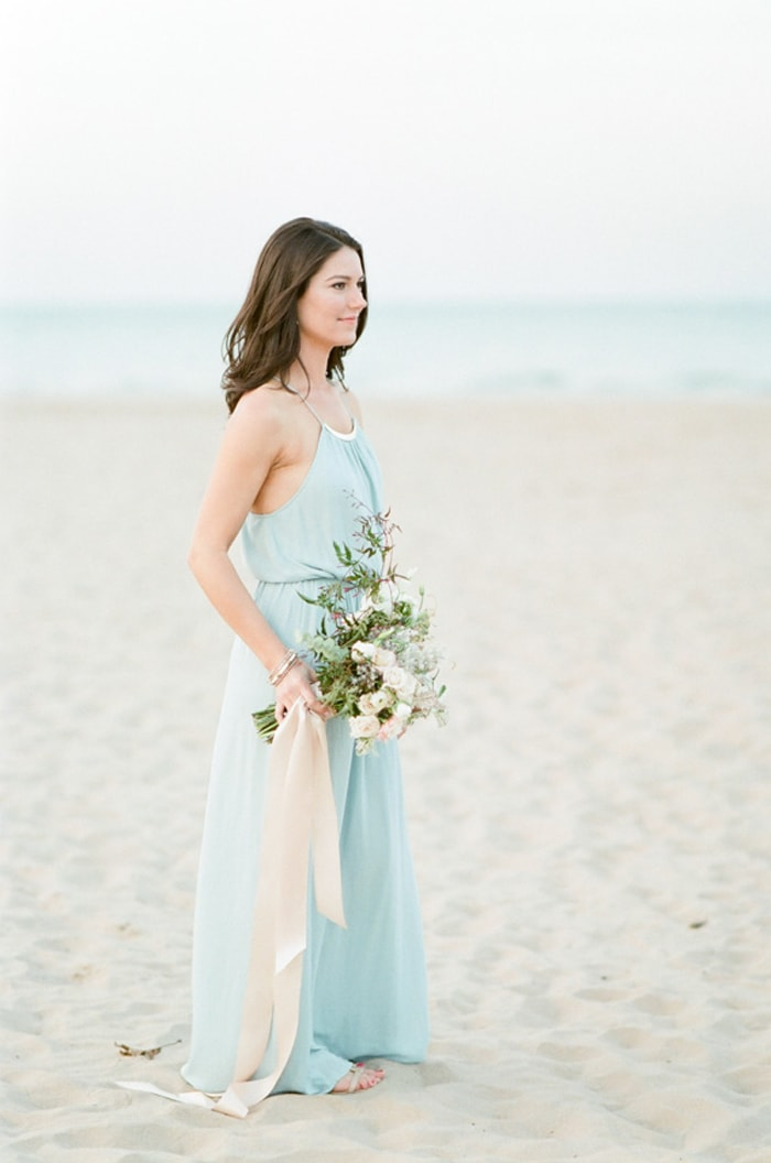 Woman at the beach in a blue dress with bouquet