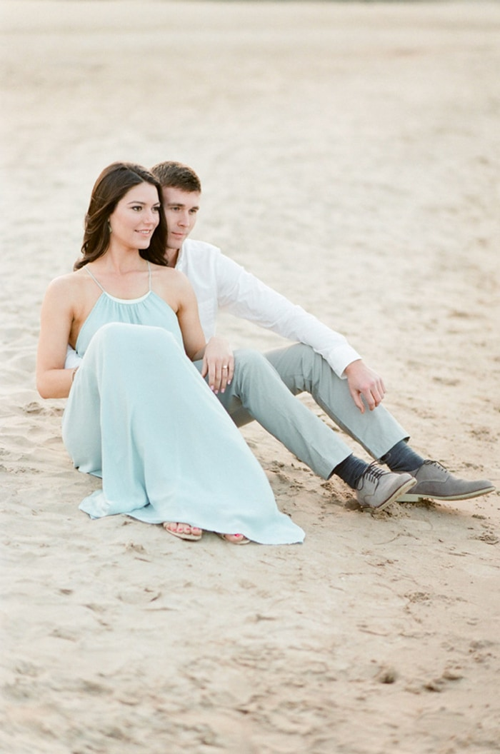 Couple relaxing while sitting on the beach