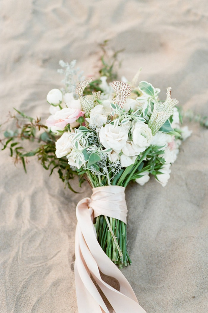 Bouquet of shades of white and green flowers on sand