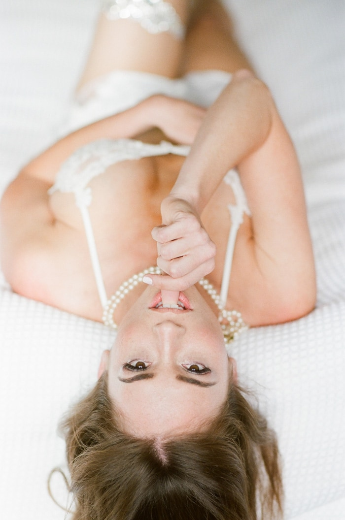 Woman wearing white lingerie laying upside down on white sheets