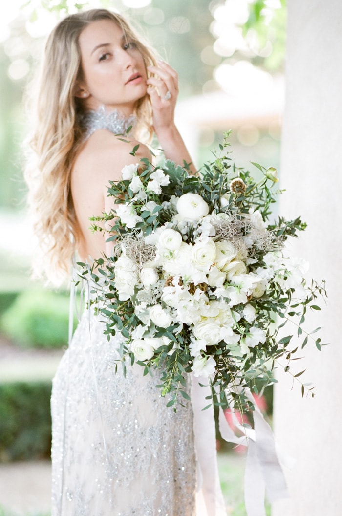 Woman holding a floral arrangement of white bouquet of flowers