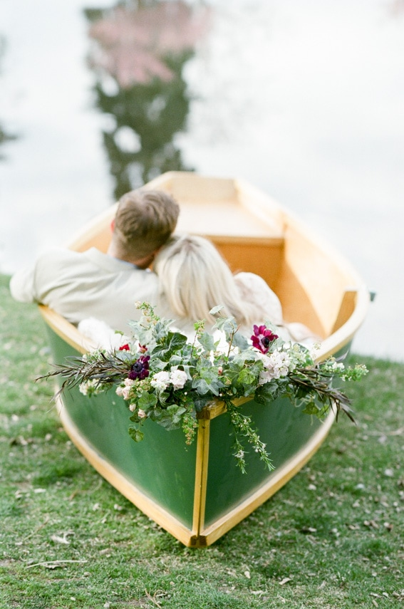 Green rowboat resting on the shore decorated with flowers with engaged couple laying inside