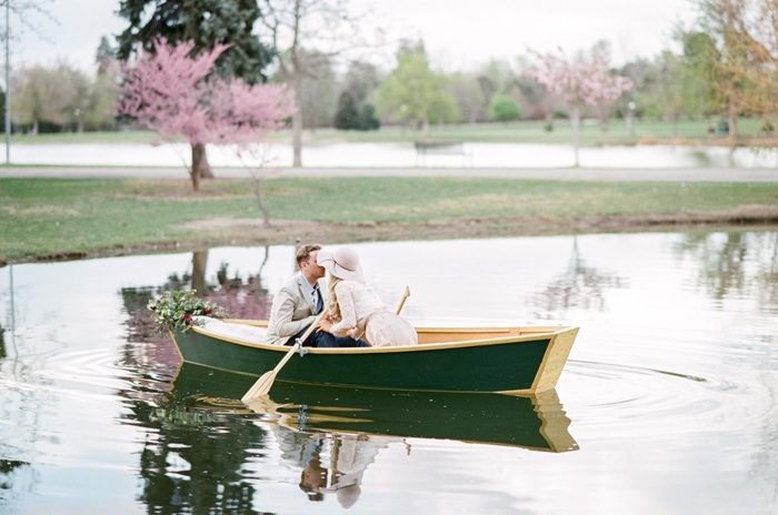 Engaged couple kissing in a green rowboat out in the water