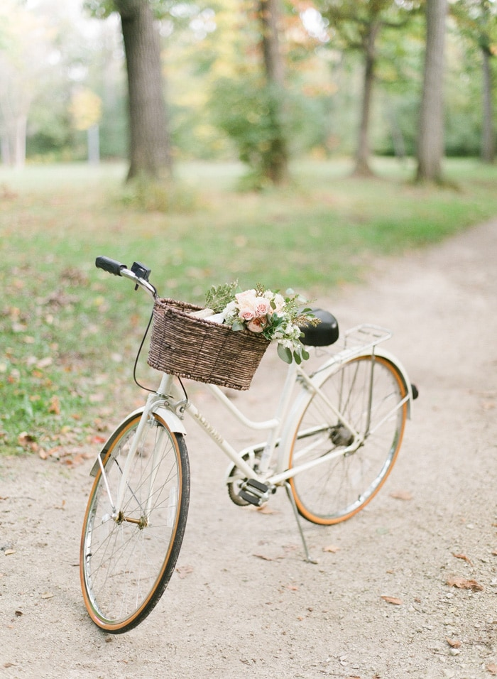 White bicycle with bouquet of flowers in basket