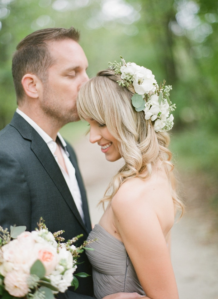 Bride-to-be with white flowers in hair and bouquet and groom-to-be kissing her