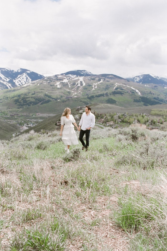 Engaged couple holding hands on Vail mountaintop