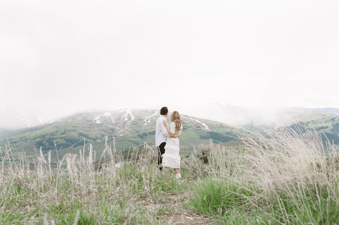 Engaged couple standing in a grass field looking off into the distance