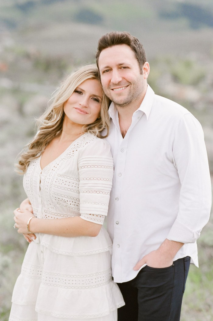 Portrait of engaged couple smiling wearing matching white outfits during their engagement portraits in Vail