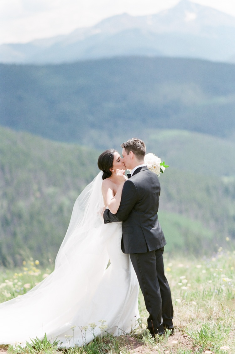 Wedding couple getting their first look at each other and kissing with scenic mountain view