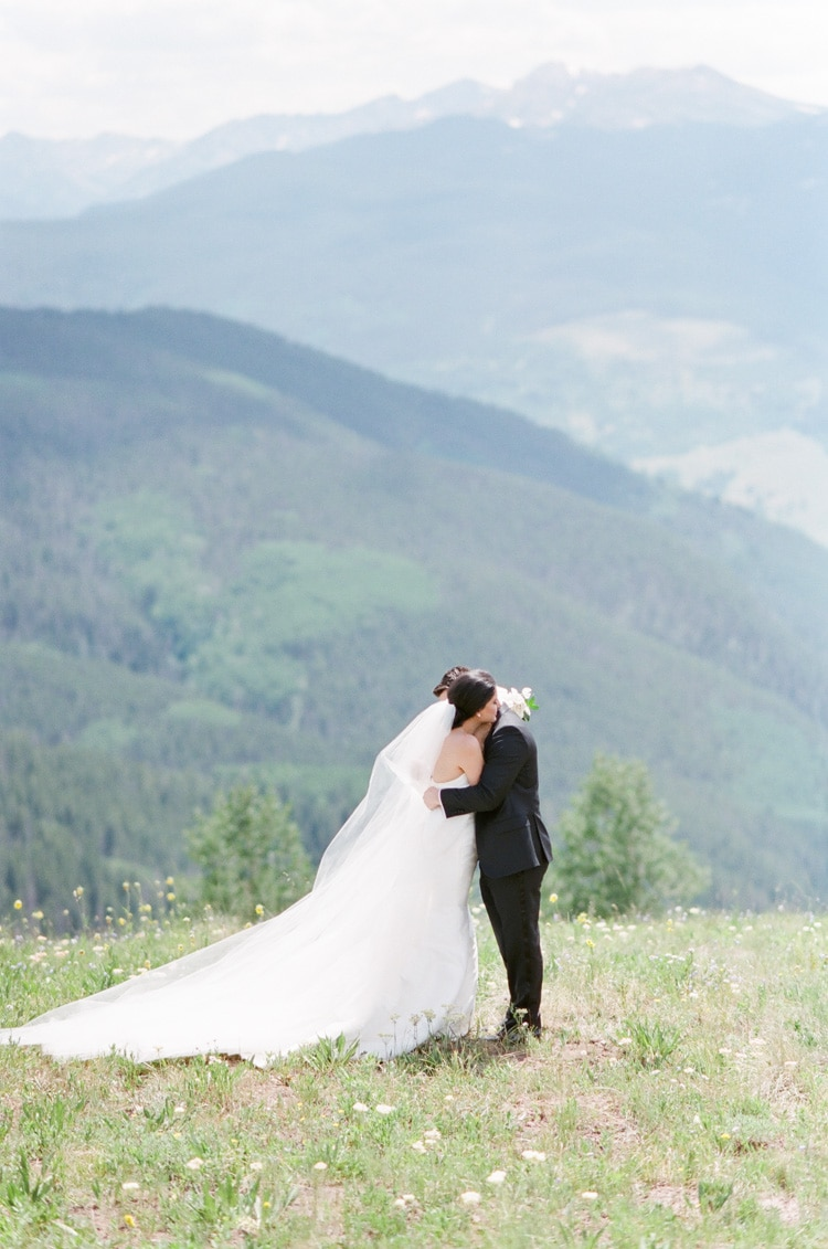 Bride and groom on wedding day embracing with backdrop of the mountains