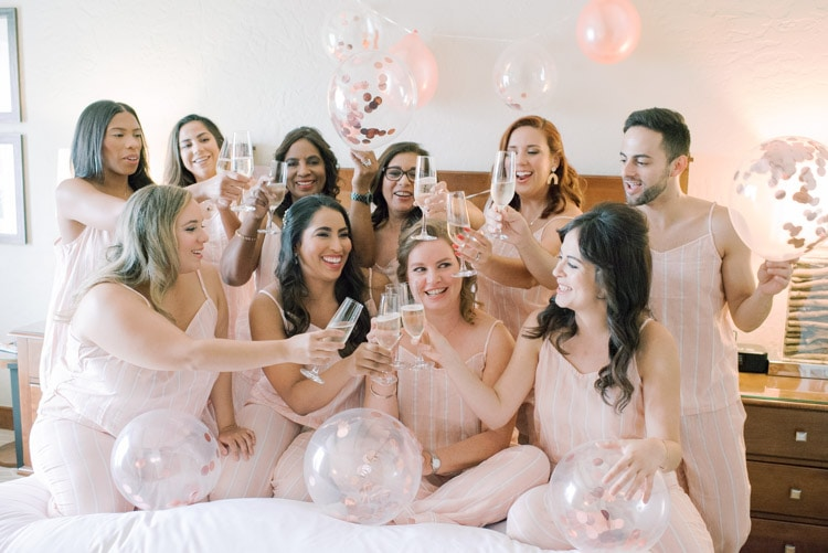 Bride and bridesmaids clinking Champagne glasses while getting ready