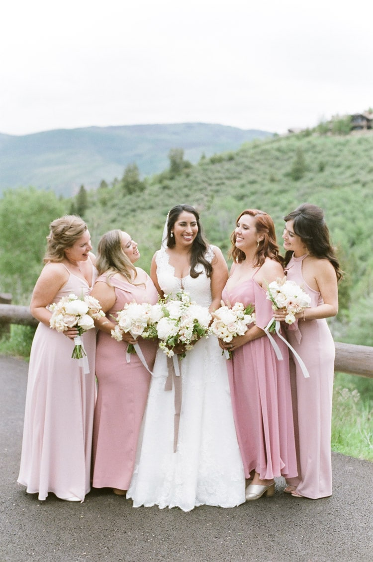 Bride with bridesmaids wearing gowns in shades of blush