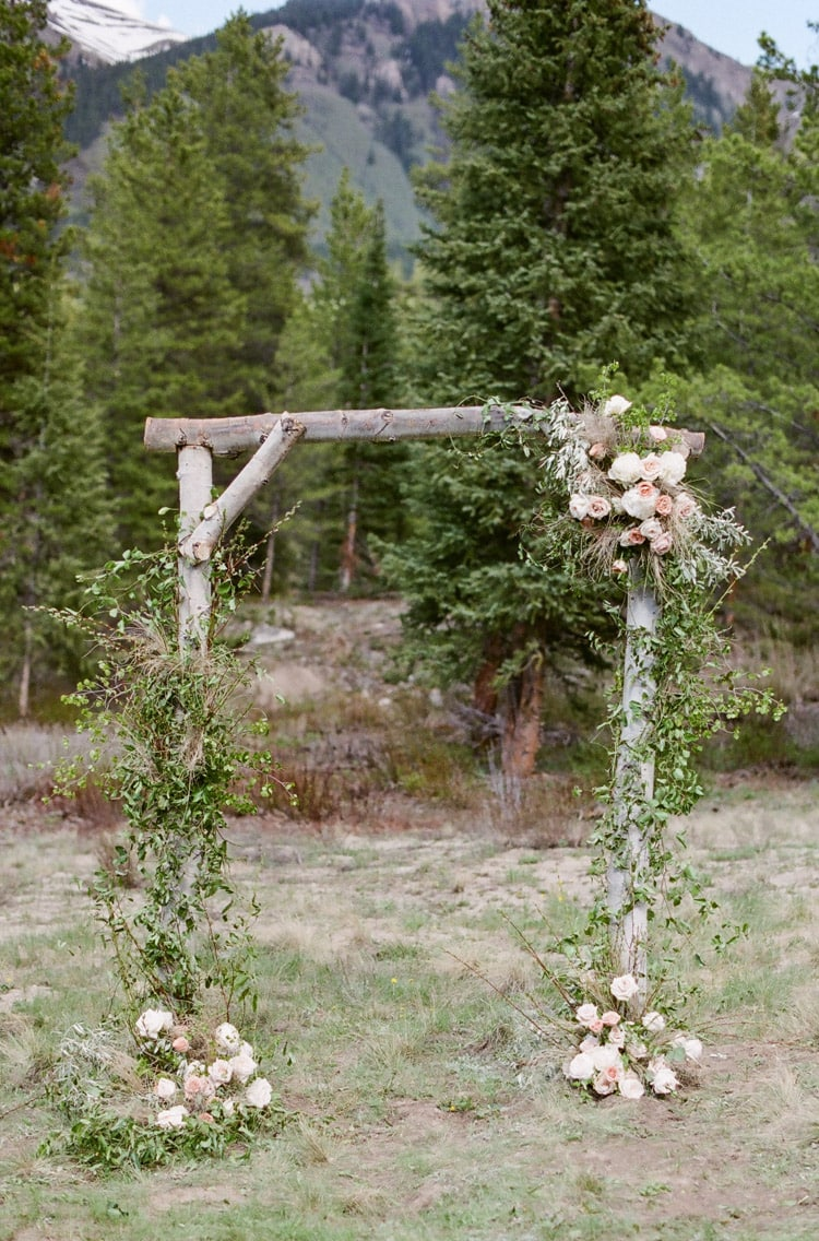 Rustic ceremony arch at an outdoor wedding in Vail