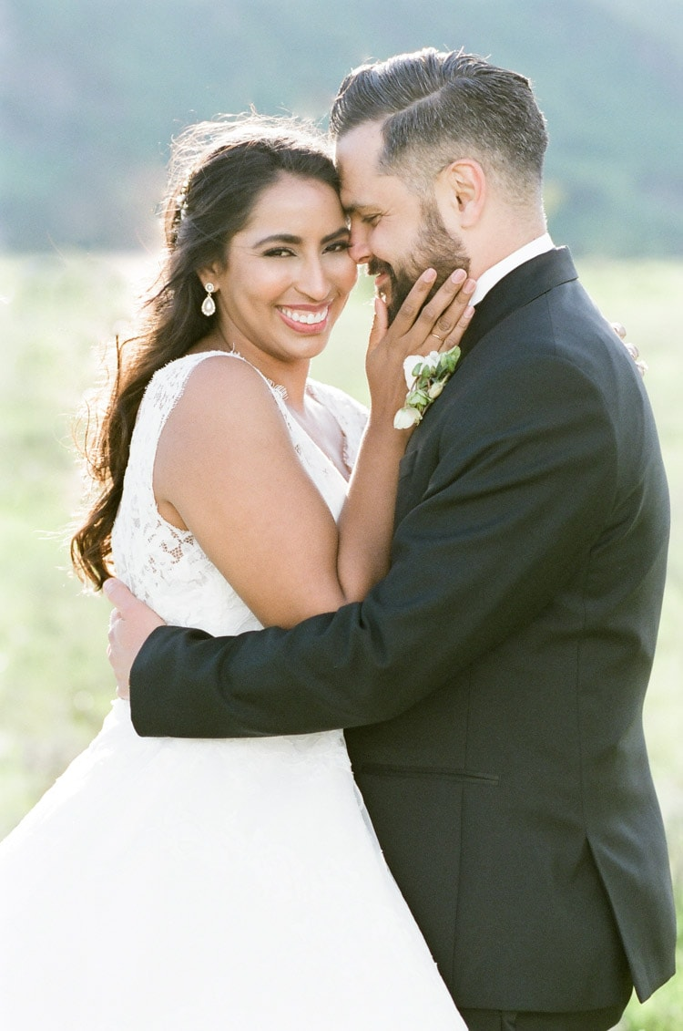 Bride and groom smiling in a field
