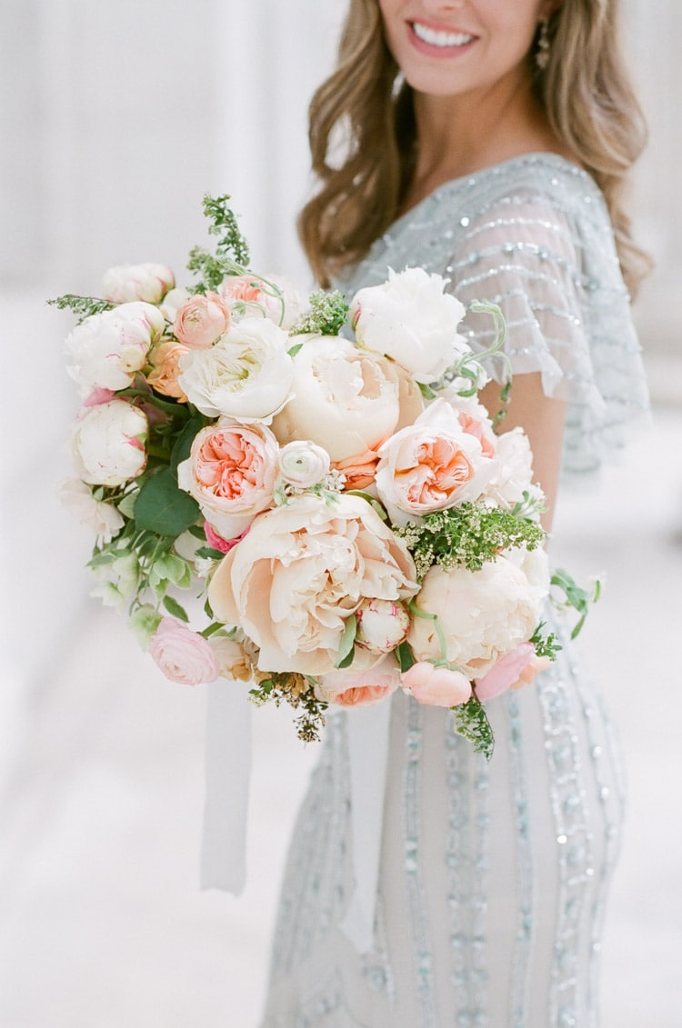 Woman in beaded dress holding classic wedding bouquet