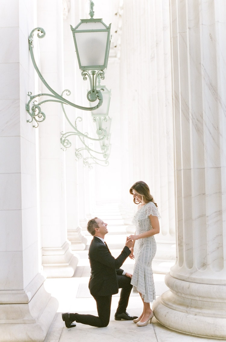 Man proposing to woman in front of the columns of the Denver courthouse