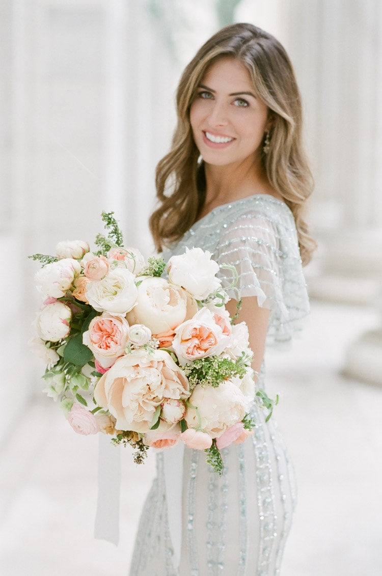 Woman holding bouquet in shades of blush and cream