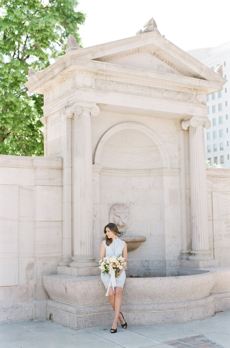 Woman sitting in front of a fountain in Denver