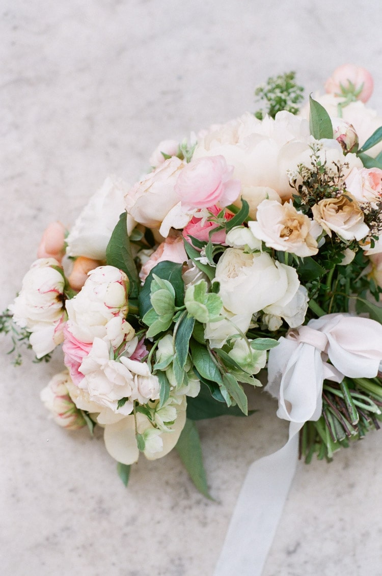 Flat lay of bouquet in shades of pink and cream with greenery