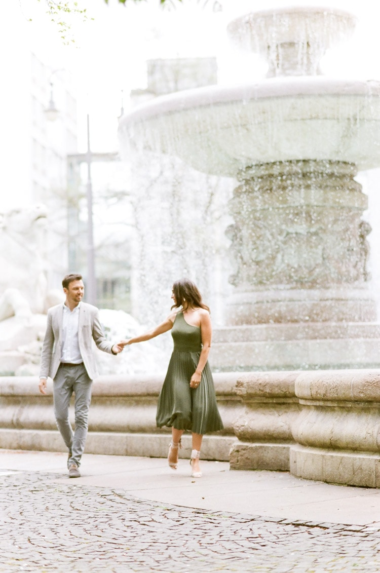 Couple dancing in front of a fountain in Munich