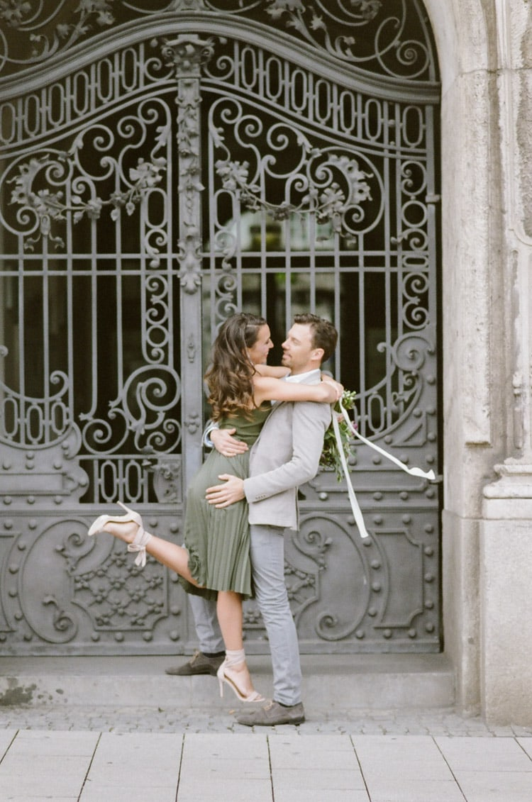 Man holding his fiance in front of an iron gate in Munich