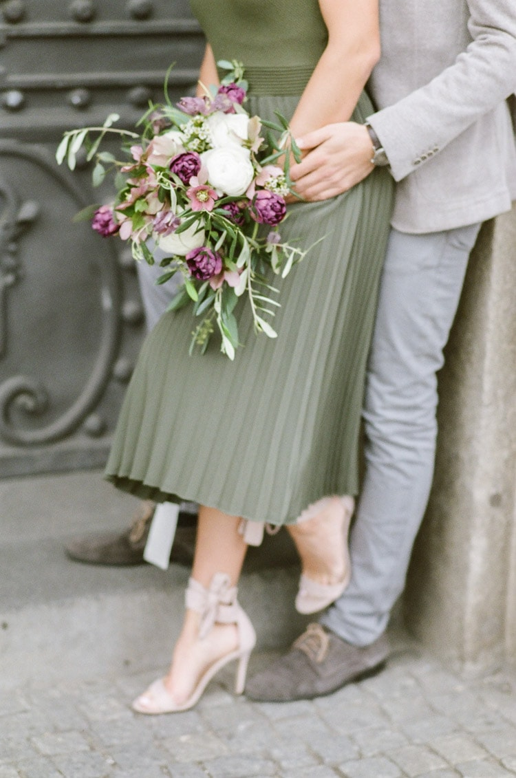 Woman leaning against her fiance and holding a bouquet during her engagement portraits in Munich