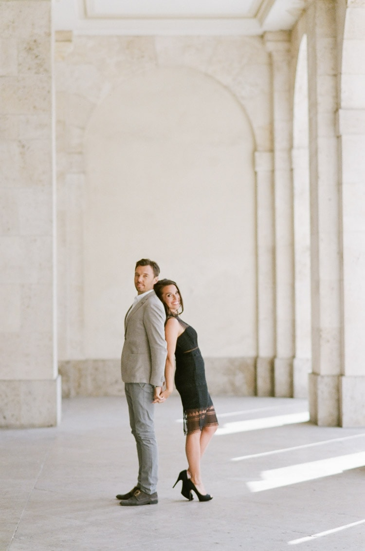 Man and woman lean against one another during their romantic destination engagement portraits in Munich