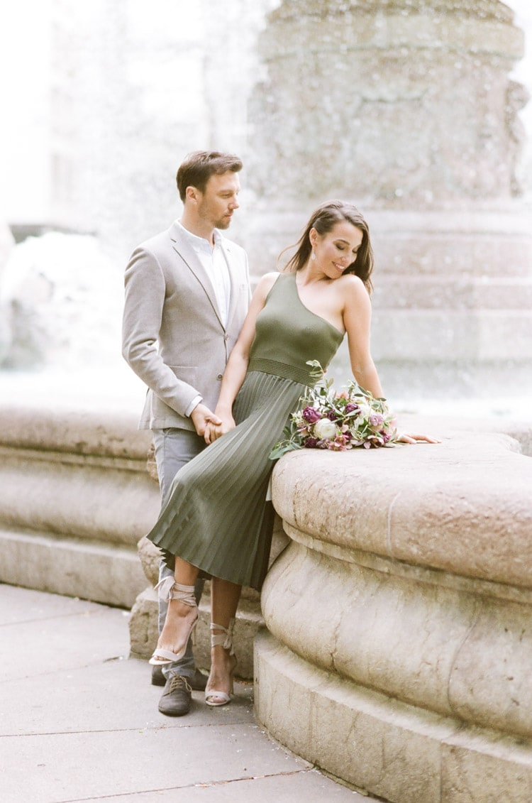 Couple sitting in front of fountain in Munich during their destination engagement portrait session