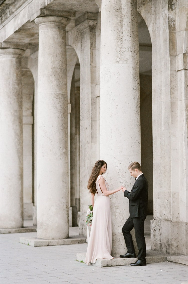 Couple standing in front of columns in Munich