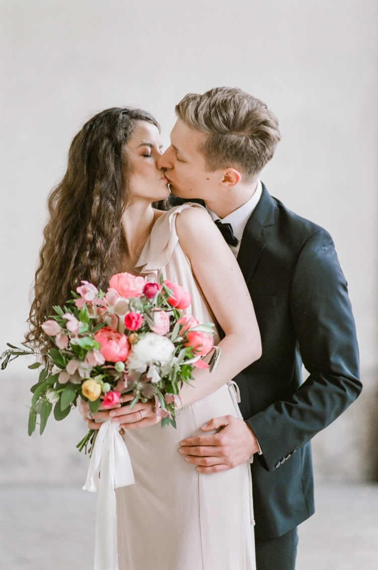 Couple kissing while woman holds a pink bouquet