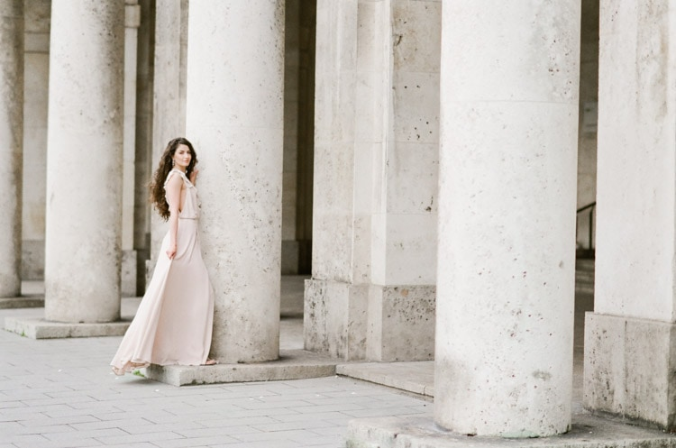 Woman in pink gown standing in front of columns in Munich